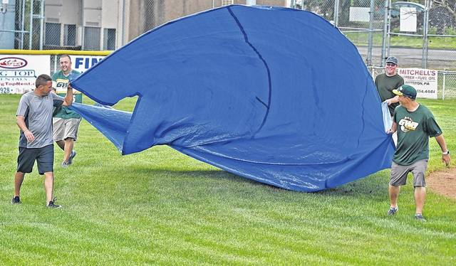 It was calm before the storm, as volunteers with West Pittston Little League prepare to cover the infield with tarps on Saturday after both district championship baseball games were postponed due to storms in the region. They are scheduled to play on Sunday at West Pittston, weather permitting. Butch Comegys   For Times Leader