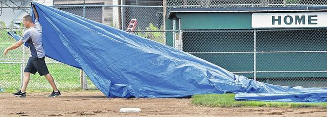 It was calm before the storm, as a volunteer with West Pittston Little League drags a tarp to cover a section of the infield on Saturday after both games were cancelled due to storms in the region. Butch Comegys   For Times Leader