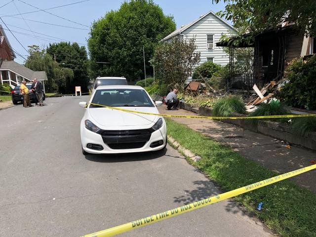 A state trooper investigating a fatal fire at 18 Wood St. in Pittston Tuesday looks at evidence found outside the charred house. Jerry Lynott | Times Leader