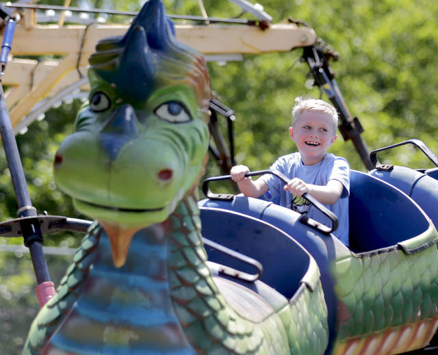 Eight-year-old Corbin Langman, of Honesdale, rides the Dragon Wagon at the Fourth of July carnival at Kirby Park on Thursday. Bill Tarutis | For Times Leader