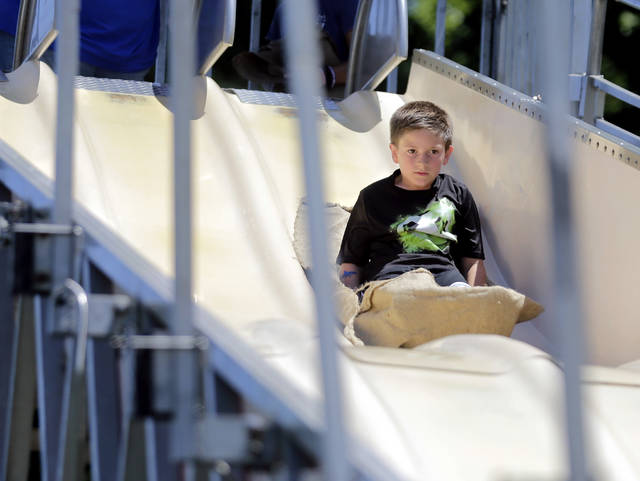Joshua Tupper, 8, of Chincoteague, Va., who is visiting his great-grandmother in Wilkes-Barre, starts his descent on the Fun Slide at the Fourth of July carnival at Kirby Park on Thursday. Bill Tarutis | For Times Leader
