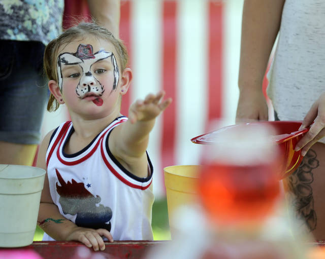Carlee Dennis, 2, of Hanover Township, tries her hand at the goldfish bowl toss at the Fourth of July carnival at Kirby Park on Thursday. Bill Tarutis | For Times Leader