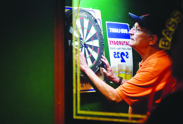 FILE PHOTO — Doc Anttonen, 78, of Millersville, retrieves darts from the board after each throw at Murphy's Pub in Swoyersville during the 2018 Keystone State Games. Bill Tarutis | For Times Leader