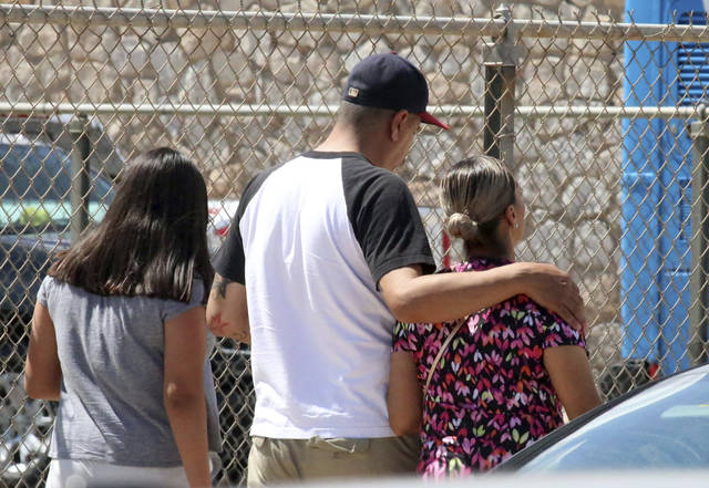 People walk out of an elementary school after family members were asked to reunite following a shooting at a shopping mall in El Paso, Texas, on Saturday, Aug. 3, 2019. Multiple people were killed and one person was in custody after a shooter went on a rampage at a shopping mall, police in the Texas border town of El Paso said. (AP Photo/Rudy Gutierrez)