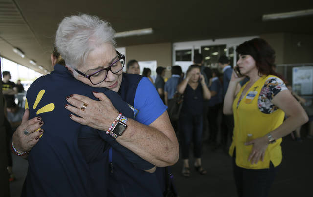 Walmart employees comfort one another after an active shooter opened fire at the store in El Paso, Texas, on Saturday.