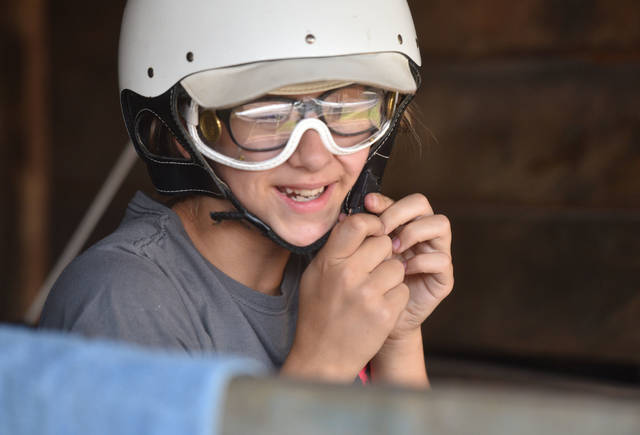 Paige McGowan, 12, of Taylor, clips on a helmet before the daily horse jogging during Harness Horse Youth Foundation Summer Camp at The Downs at Mohegan Sun Pocono. Aimee Dilger   Times Leader