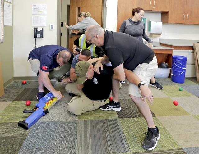 Participants swarm 'active shooter' Henry Giammarco, senior supervisory special agent with the state attorney general's office, during an ALICE active shooter training exercise at Bear Creek Community Charter School on Wednesday. Bill Tarutis | For Times Leader