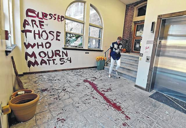 Melissa Reed from Planned Parenthood leaves the area of the Wilkes-Barre office that was vandalized. A man smashed doors and windows left a burnt book and wrote on the wall with paint. Aimee Dilger | Times Leader