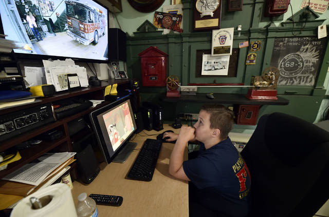 Brian Lyons, 10, watches a security camera at the Elm Hill Hose Co No. 3. Lyons has been selling lemonade to raise $9,514 to buy the department a Jaws of Life. Lyons has raised more than $6,500 so far. Aimee Dilger | Times Leader