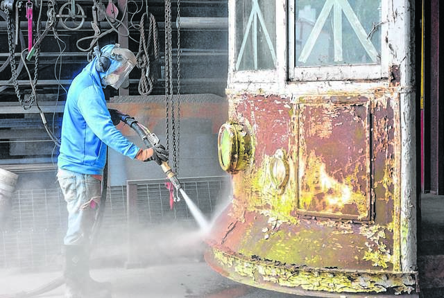 Vincent Shea of Bieber Dustless Blasting removes old paint and rust from Wilkes-Barre trolley 790 on July 3. Volunteers working to restore the trolley are planning a fundraiser for next month. Times Leader file photo