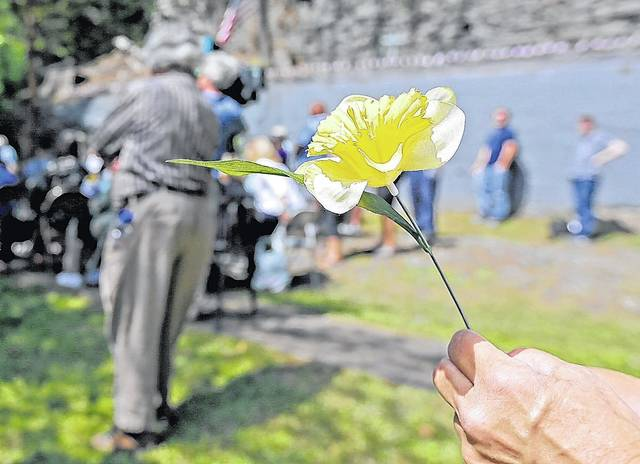 A woman holds a flower during the 150th anniversary commemorative service of the Avondale mine disaster Sunday in Plymouth Township. Bill Tarutis | For Times Leader