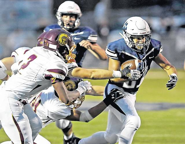 Berwick running back Alejandro Lopez slithers through the Wyoming Valley West defense Friday night in Berwick. Bill Tarutis | For Times Leader