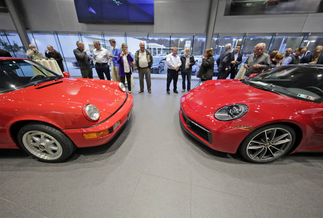 'The past meets the future' as guests look over a 1994 Porsche RS America, left, and a 2020 911 coupe at Porsche of Wyoming Valley in Plains Township on Tuesday evening. Bill Tarutis   For Times Leader