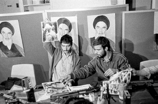 In this Nov. 5, 1979, file photo, Ebrahim Asgharzadeh, left, a representative of the Iranian students who stormed the U.S. Embassy on Nov. 4, holds up a portrait of one of the blindfolded hostages, during a news conference in the embassy in Tehran. Posters of the Islamic Revolution leader Ayatollah Ruhollah Khomeini adorn the wall. The man at right is unidentified. Speaking to The Associated Press ahead of the 40th anniversary of the attack, Asgharzadeh acknowledged that the repercussions of the crisis still reverberate as tensions remain high between the U.S. and Iran over Tehran's collapsing nuclear deal with world powers. AP photo