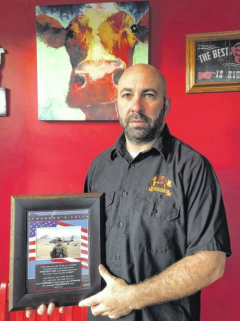 Dominick Aritz Jr. holds a collage dedicated to his time in the military. Roger DuPuis | Times Leader