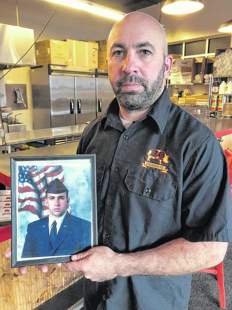 Dominick Aritz Jr. holds a photo of himself from 20 years ago. Roger DuPuis | Times Leader
