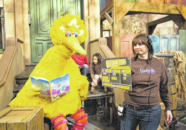 This April 10, 2008 file photo shows Lynn Finkel, stage manager for 'Sesame Street,' slating a taping with Big Bird in New York.
