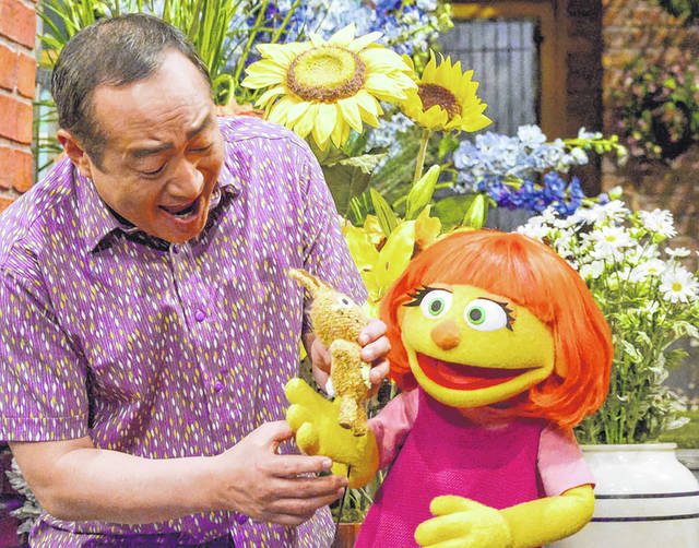 This image released by Sesame Workshop shows castmember Alan Muraoka, left, with Julia, an autistic muppet character.
