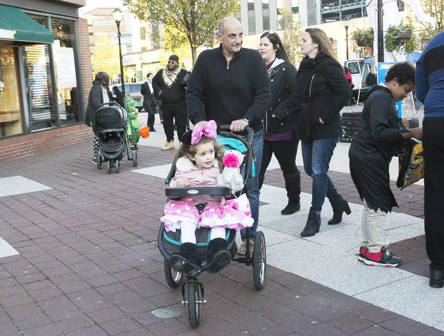 Wilkes-Barre Mayor Tony George walks around with his grandaughter Emily, 3, during Friday's trick-or-treating event on Friday. Amanda Hrycyna | For Times Leader