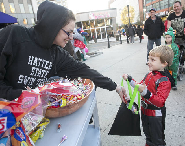 Demi Dennis of Rodano's hands out candy to Caleb Ketron, 4 of Wyoming during Wilkes-Barre's trick-or-treat event Friday night.  Amanda Hrycyna | For Times Leader