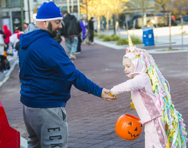 Steve Pugliese, a member of the Wyoming Valley Car Club, hands out candy to Clover Yost, 5, of Plymouth. Amanda Hrycyna | For Times Leader