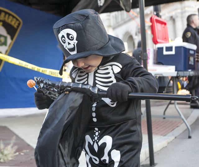 Tyler Grissom, 3 of Wilkes-Barre looks into his candy bag to see all the treats he collected Friday night during the city's Halloween event downtown. Amanda Hrycyna | For Times Leader