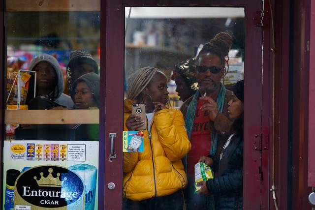 Bystanders look out from a store as law enforcement arrives at the scene following reports of gunfire Tuesday in Jersey City, N.J. AP photo