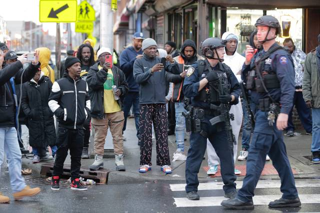 Bystanders look on as law enforcement arrive on the scene following reports of a shooting Tuesday in Jersey City, N.J. AP photo