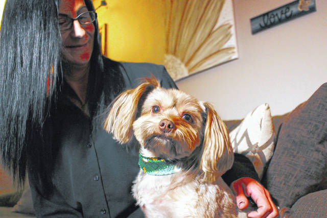 Amy Carter looks at her Yorkshire terrier-Chihuahua mix Bentley, who has epilepsy. Carter, gives him CBD, which she says has reduced his seizures. AP photo