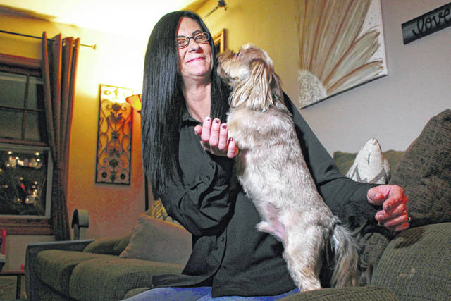 Amy Carter lets her dog Bentley lick her face at her home in St. Francis, Wis. Carter gives him CBD, which she says has reduced his epilepsy-related seizures. AP photo