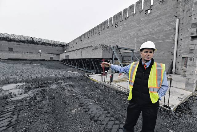Wilkes-Barre Area School District Brian Costello points out to what will be the gym at the Wilkes-Barre Area high school. Support for much of a second floor track can be seen ringing the walls Aimee Dilger | Times Leader