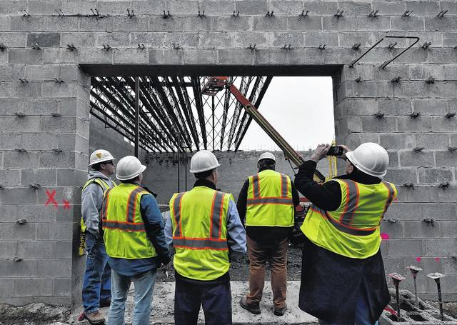 Members of the school district and media look at work being done in the auditorium at the new Wilkes-Barre Area high school. Small eye hooks jut out from the mortar between cement block. They will help anchor the brick facade that will cover the block. Aimee Dilger | Times Leader