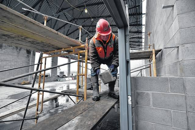 A worker lays brick in the library of the new Wilkes-Barre Area consolidated high school in Plains Township. Aimee Dilger | Times Leader