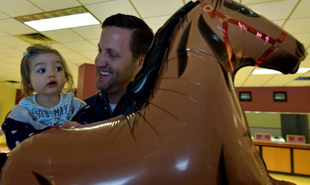 Harness driver Simon Allard holds Fallon Janine as she plays with a horse balloon at The Downs at Mohegan Sun Pocono on Thursday. Allard was on hand for a press conference announcing the start of the harness season on Saturday.                                  Aimee Dilger   Times Leader