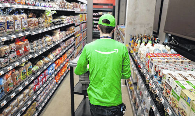A worker pushes a cart inside an Amazon Go Grocery store set to open soon in Seattle's Capitol Hill neighborhood. Following the opening of several smaller convenience-type stores using an app and cashier-less technology to tally shoppers' selections, the store will be the first Amazon Go full-sized cashier-less grocery store.                                  AP photo