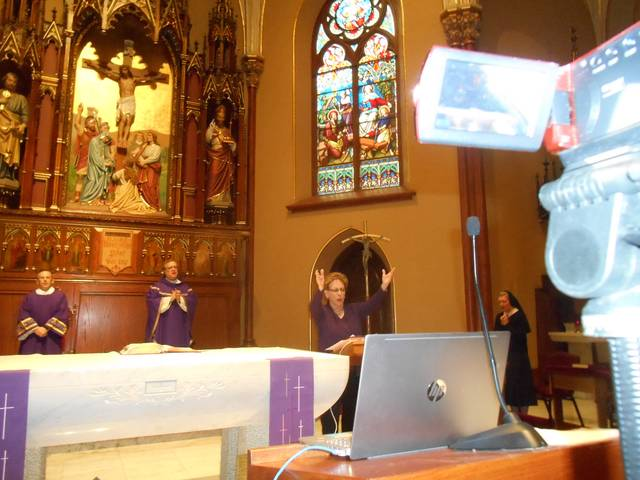 <p>Cantor Mary Pat Brunner raises her arms as she sings the refrain of a psalm. Also on the altar at St. Nicholas Church are, from left, Deacon Mike Golubiewski, the Rev. Joseph Verespy and Sister Maria Angeline.</p> <p>Mary Therese Biebel | Times Leader</p>