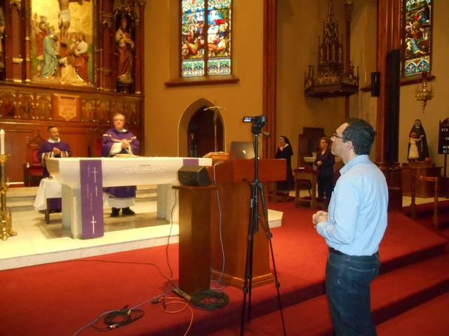 <p>Joe Sudano, in foreground at right, stands ready to adjust a camera that is trained on the altar at St. Nicholas Church in Wilkes-Barre, where chuch pastor the Rev. Joseph Verespy celebrated Mass on Sunday.</p> <p>Mary Therese Biebel | Times Leader</p>