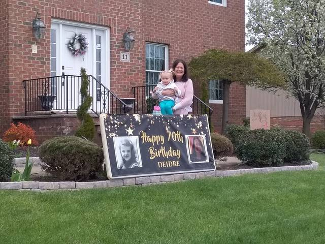 <p>Deidre Miller Kaminski with her granddaughter Amelia as they watch a caravan of friends parade by to celebrate her birthday on Thursday.</p>