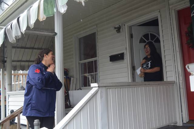 <p>Coughlin High School teacher Genelle Hoban-Sedon shares a laugh with student Noemi Galeno on the porch of Galeno's home on April 24. Hoban-Sedon decided to hand deliver personalized cards and a donut to the seniors in her class, believing they deserved a little treat to sweeten the remote learning lessons they are getting with schools closed by the COVID-19 pandemic.</p>                                  <p>Mark Guydish | Times Leader </p>