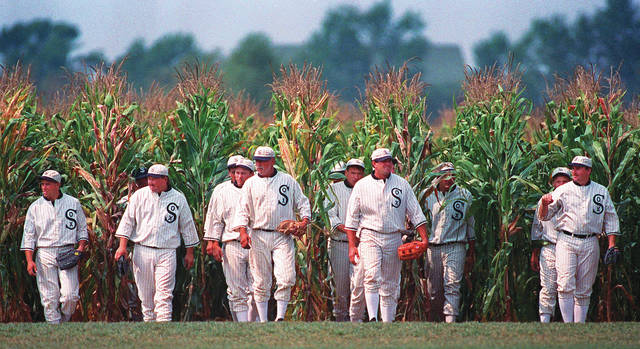 "People portraying ghost players emerge from a cornfield as they reenact a scene from the movie ""Field of Dreams"" at the movie site in Dyersville, Iowa. The 1989 film was No. 6 in The Associated Press' Top 25 favorite sports movies poll. AP photo"