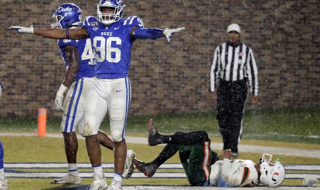 In this Nov. 30, 2019 file photo, Duke's Chris Rumph II (96) celebrates in front of Miami's Jarren Williams (15) after Duke made a defensive stop during the third quarter of an NCAA college football game in Durham, N.C. Football players and other college athletes are facing challenges when it comes to following nutrition plans amid the coronavirus pandemic. Rumph has been staying with family and eating home-cooked meals as he tries to gain strength amid the pandemic that has shut down college and professional sports.