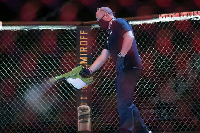 <p>A worker sprays sanitizer in the octagon between bouts during a UFC 249 mixed martial arts competition Saturday in Jacksonville, Fla.</p> <p>AP photo</p>