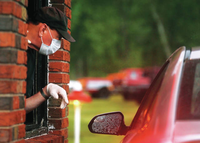 <p>George Bobey works the ticket booth at the Garden Drive-In in Hunlock Creek on Friday night. Due to the COVID-19 pandemic, Bobey not only sold tickets but gave parking instructions to drivers as they entered the theater.</p>