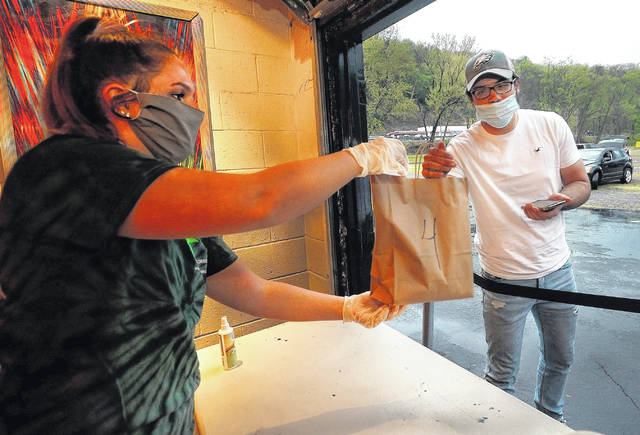 <p>Brook Martin, a server at the Garden Drive-In concession stand, hands Raymond Salwoski, 21, of Hanover Township, his food order Friday night.</p> <p>Fred Adams | For Times Leader</p>
