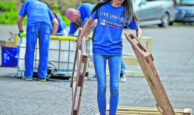Volunteer Josie Lent, 39, of Mountain Top, carries sections of a child's bed made of pine wood during the annual United Way of Wyoming Valley's Day of Caring event last year at the Power Engineering Corporation in Plains Township. Times Leader file photo
