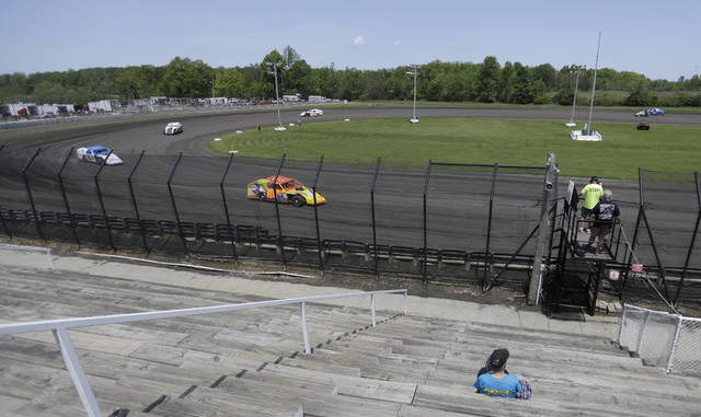 A fan watches as cars practice on a short dirt track at Gas City I-69 Speedway on Sunday in Gas City, Ind. AP photo