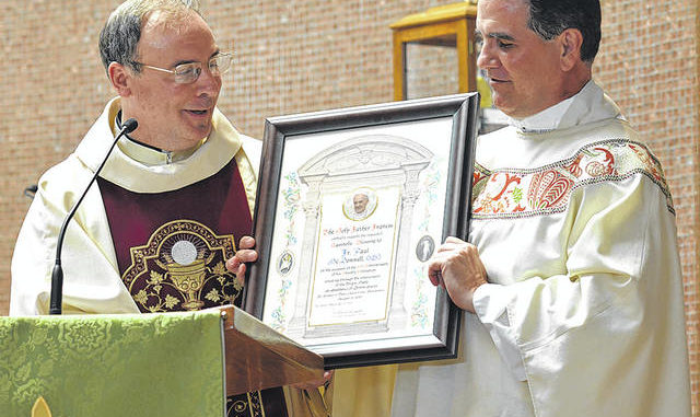 Father McDonnell's longtime friend and fellow priest, Father Brian Crawford, presents an Apostalic Blessing from Pope Francis during Father McDonnell's 25th anniversary as an ordained priest. Tony Callaio | For Sunday Dispatch