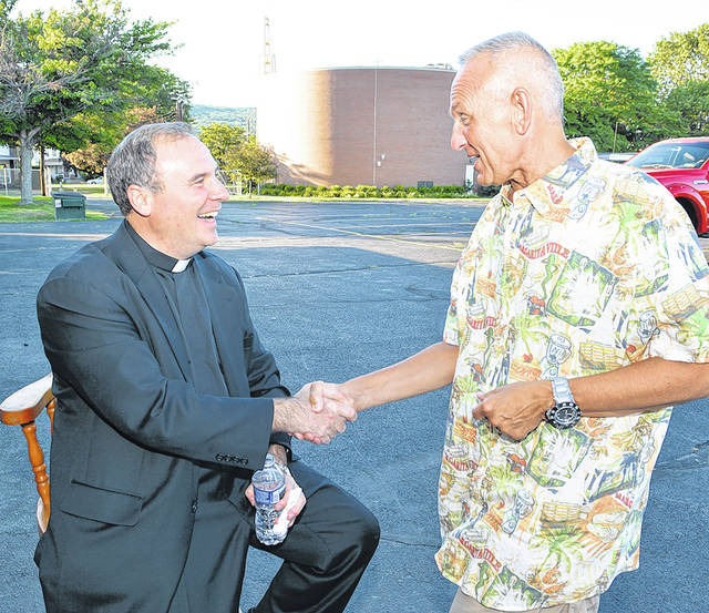 <p>Late state Rep. Sid Michaels Kavulich congratulates Father Paul McDonnell on his 25th anniversary as a Roman Catholic priest in 2016.</p> <p>Tony Callaio | For Sunday Dispatch</p>