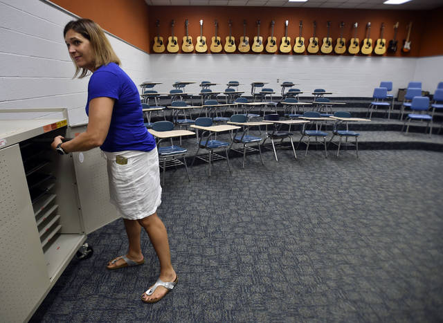 <p>Chorale instructor Joelle DeLuca in shown in this file photo putting away laptops in the chorale room.</p> <p>Times Leader File Photo</p>