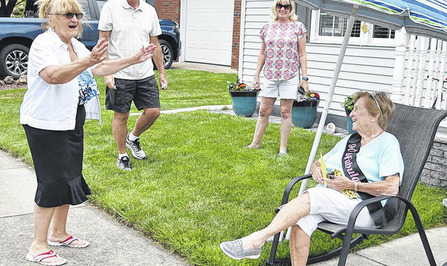 Marianne Argenio, left, neighbor of Joe and Lisa Gillespie, center, wishes Joan Pribula a happy 90th birthday where a vehicle parade drove by honoring Mrs. Pribula. Tony Callaio   For Sunday Dispatch